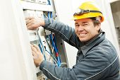 stock photo of electrician  - One electrician builder at work installing energy saving meter into electric line distribution fuseboard - JPG