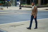Young successful African - American business man walking in the city
