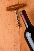 Cabernet Sauvignon bottle and corkscrew on a wooden table. The antique opener and bottle are at an angle leaving room for copy. Only half the bottle is in the frame.