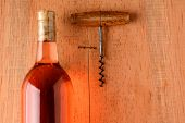 A blush wine bottle and corkscrew on a rustic wood surface with strong side light. Closeup in horizontal format with copy space.