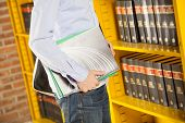 Midsection of young student holding books in college library