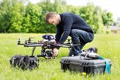 stock photo of helicopters  - Young engineer setting SLR camera on UAV helicopter at park - JPG