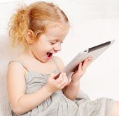Child with tablet computer. Little child playing at home on sofa