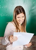Happy female student looking at exam result against greenboard in classroom