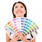 stock photo of gamma  - Thoughtful woman holding a color guide  - JPG