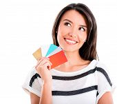 Thoughful shopping woman with credit cards - isolated over white