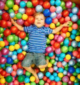 Happy child playing at colorful plastic balls playground high view