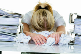 picture of shy woman  - a young woman desperately in office between many file folders and crumpled papier - JPG