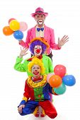 Three People Dressed Up As Colorful Funny Clowns Over White Background