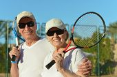 stock photo of elderly  - Happy elderly couple with tennis racket in hand - JPG
