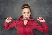 foto of whip-hand  - Beautiful fashion woman in the red blouse with whip in her hands - JPG
