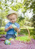 Cute Little Boy Wearing Hat Enjoying His Easter Eggs on Picnic Blanket Outside in the Park.
