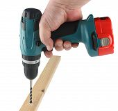 picture of hand drill  - Cordless drill in his hand drill hole wooden beams - JPG