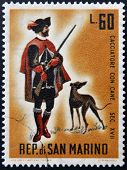 SAN MARINO - CIRCA 1961: A stamp printed in San Marino dedicated to hunting shows Hunter with dog
