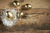 golden easter eggs in nest on vintage rustic wooden background