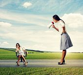 emotional woman screaming at tired woman on the road