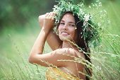 Young beautiful woman wearing herbal wreath enjoying in green spring field