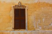 Ciutadella Menorca wooden shutter window on grunge yellow downtown wall at Balearic islands