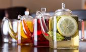 picture of black tea  - three square teapots with different colors fruit tastes of tea - JPG