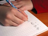 Closeup on the hands of a child doing math homework