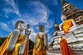 Praying Buddhas at Wat Yai Chai Mongkhon temple under blue sky. Ayutthaya Thailand
