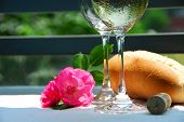 Two wine glasses with white wine, table setting outside