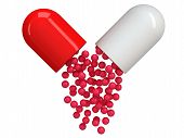 Opened red white pill capsule with crimson granules