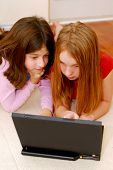 Portrait of two girls lying on the floor and  looking into computer