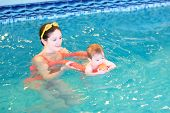 Baby Playing With Her Mother In An Early Swimming Class