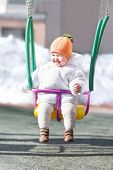 Happy Baby In A Swing On A Sunny Winter Day