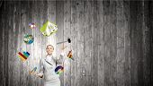 Young pretty businesswoman juggling with white balls. Elements of this image are furnished by NASA