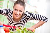 picture of supermarket  - Attractive young woman smiling and pushing a cart at supermarket - JPG