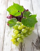 Grapes on wooden table, close-up.