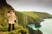 Irish Atlantic Coast. Woman Tourist Standing On Rock Cliff