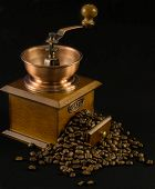 An old fashioned coffee grinder with coffee beans on isolated background