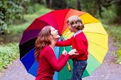 Mother And Son Playing Under A Colorful Umbrella
