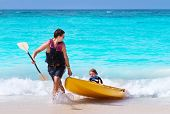 Father And Son Kayaking Together On A Tropical Beach