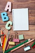 stationery objects with word abc on wooden background