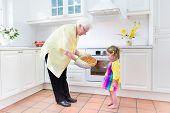 Happy Grandmother And Little Girl Baking A Pie In A White Kitchen