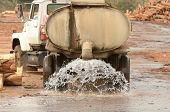 stock photo of tank truck  - large truck pulling a water tank spraying for dust control at a log yard at a lumber processing mill that specializes in small logs - JPG