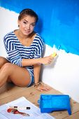 Happy beautiful young woman doing wall painting,sitting on the