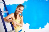Happy beautiful young woman doing wall painting, sitting on lad
