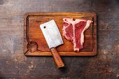 Raw Fresh Meat T-bone Steak And Meat Cleaver On Cutting Board On Dark Wooden Background