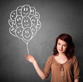 Young woman holding a bunch of smiling balloons