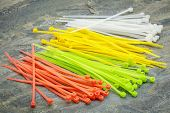 self-locked plastic zip cable ties in different colors over slate rock background