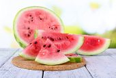 Watermelon on cutting board on wooden table on natural background