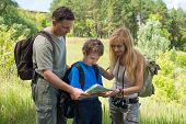 Hiking family with backpacks in the forest discussing the route. Happy couple with son looking at th