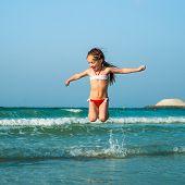 Happy little girl having fun in the sea