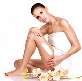 beautiful young woman with flowers using the cream. isolated on white