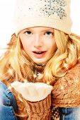 Portrait of a happy ten years girl in warm clothes holding snow. Isolated over white.